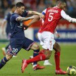 Penyerang Paris Saint-Germain Lionel Messi (kiri) berebut bola dengan pemain Reims Yunis Abdelhamid dalam pertandingan Ligue 1 Prancis, Senin (30/8) dini hari WIB.